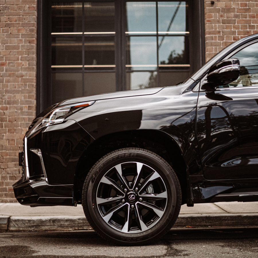 2021 Lexus LX 570 S exterior parked on a damp street. Showcasing alloy wheels.